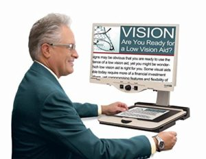 Senior man using a Merlin HD desktop electronic magnifier by Enhanced Vision